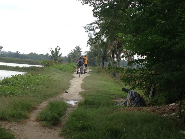 Travellers ride bicycle on the road (Tra Que Vegetable Village, Hoi An, Vietnam)
